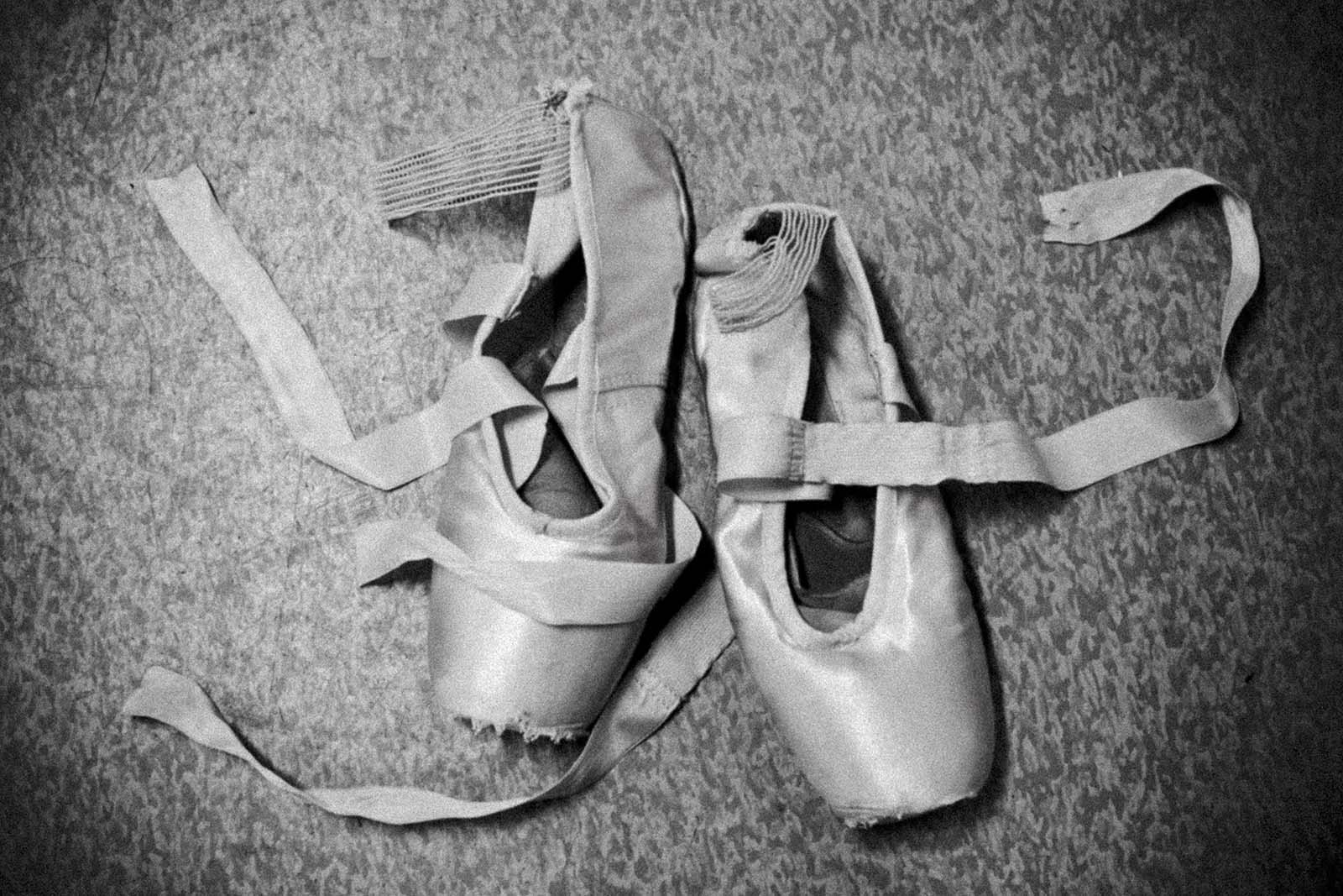 A pair of worn out ballerina shoes on the floor.